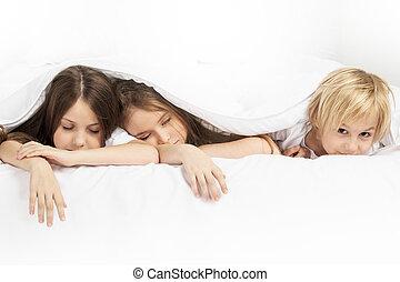 Three children sleeping in bed