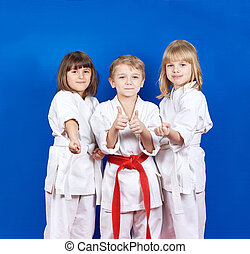 Three children standing in karate rack and showing finger super