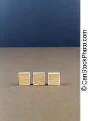 Three children wooden blocks in line, portrait