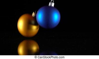 Three christmas balls falling on black background, slow...