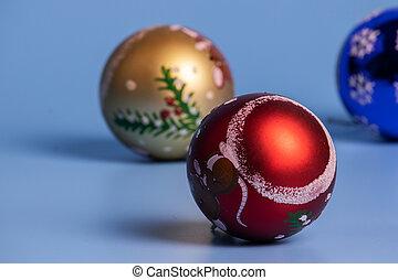Three Christmas balls on a blue background.