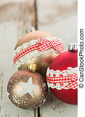 Three Christmas baubles on rustic wood