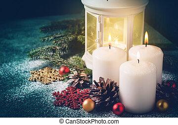 Three Christmas burning candles and lantern on dark turquoise background