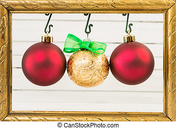 Three Christmas globes hanging on photo frame