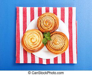 Three cinnamon rolls on white plate