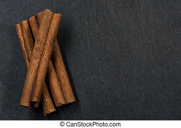 Three Cinnamon Sticks on Black Background with Copy Space to Right