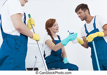 Three cleaners talking - Three young professional cleaners...