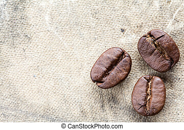 Three coffee beans on canvas background
