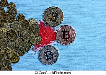 three coins bitcoin on a blue table and red sand at a pile of coins