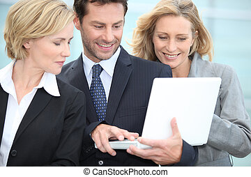 Three colleagues stood outside using laptop computer
