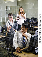 Three college students in library computer room