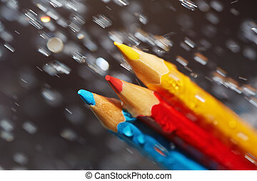Three color pencils under the rain