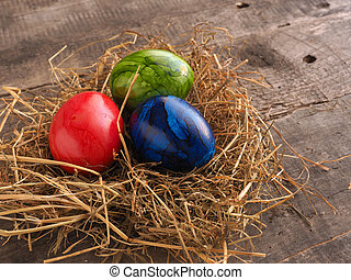 Three colored Easter eggs in a nest