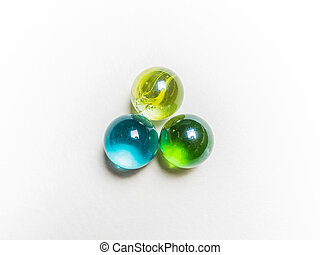 Three colored glass balls with caustics on a white background
