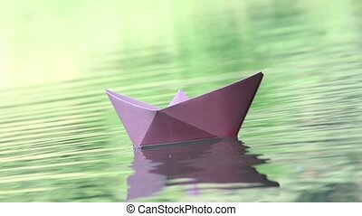 Three colored paper boats floating on water