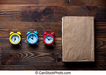 Three colorful alarm clocks and book