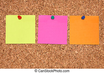 Three colorful blank notes on a notice board.