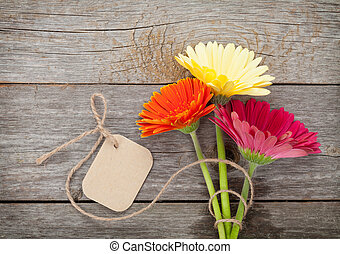 Three colorful gerbera flowers with tag