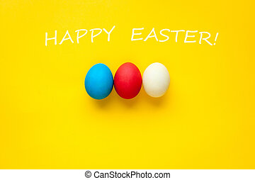 Three colorful handmade easter eggs isolated on a orange background. With the words happy Easter