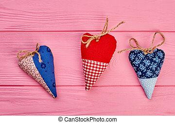 Three colorful handmade hearts.