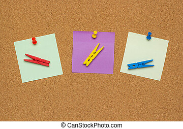 Three colorful notes with pushpins and clothespins isolated on a cork background