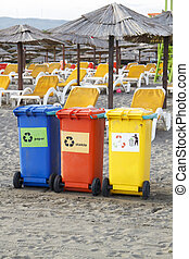 Three colorful recycle bins on the beach