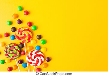 Three colorful round candies on sticks over yellow background with copy space. Closeup view