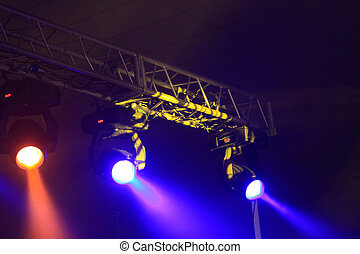 Three coloured rotary spotlights on yellow beam in a concert hall