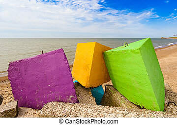 Three different colours - purple, yellow and green concrete breakwater blocks on the beach, in the backgroundblue cloudless sky, yellow sand and coastline.