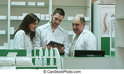 Three concentrated pharmacists using tablet computer at a counter in a pharmacy