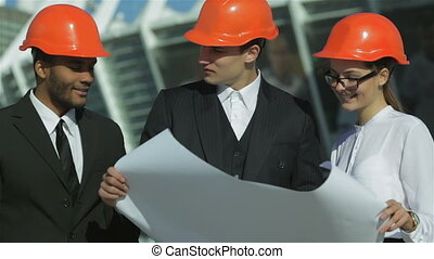 Three confident business architect in protective helmet