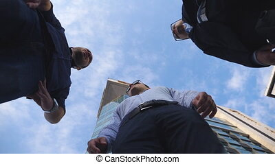 Three confident businessmen stand near office building and talking. Successful business partners meet and speak at city. Conversation between young colleagues. Blue sky at background. Low angle view.