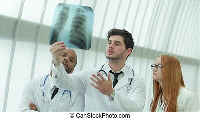 Healthy lungs and the dangers of smoking. Three confident doctor examining x-ray snapshot of lungs.