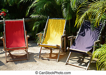 three confortable different colored beach chairs - three ...
