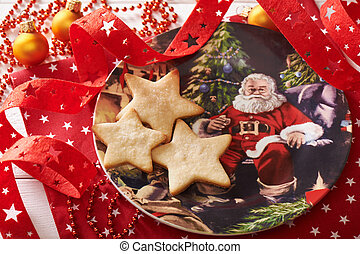 Three cookies in the form of a star on decorative plate surrounded by Christmas decorations