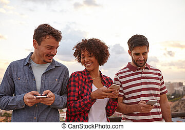Three cool friends looking at cell phones