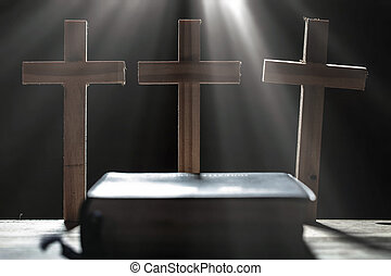 Three cross and holy Bible on wooden table in the morning. christian concept.