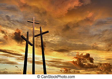 Three crosses on a hill over bright sunset