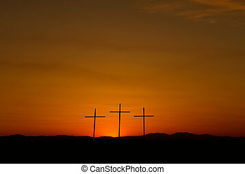 Three crosses on a hill over bright sunset with copy space