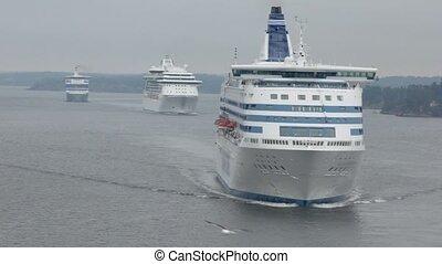 Three cruisers float beside coastline near Stockholm