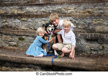 Three Cute Blonde Children Hugging Pet German Shepherd Dog Outside at Park