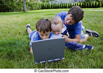Three cute brothers study on computer
