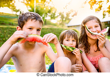 Three cute children eating watermelon in sunny summer garden