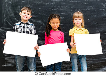 three cute children with empty paper sheets in hands