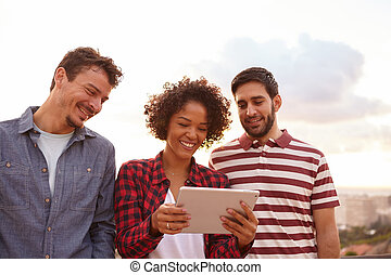 Three cute friends looking at tablet