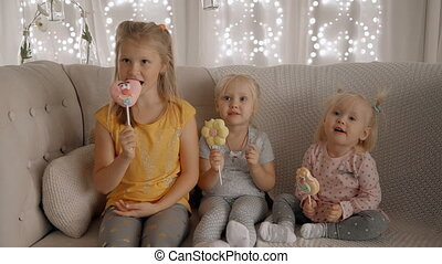 Three cute girls are eating lollipops and sweets with good...