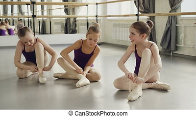 Three cute girls are trying to put on ballet slippers...