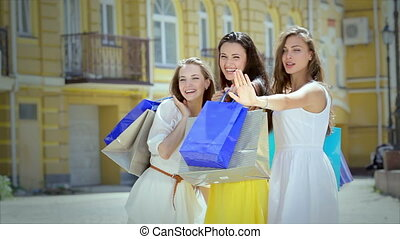 Three cute girls emotionally greet their friends while shopping