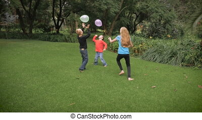 Three cute kids playing together in a park with balloons in slowmo