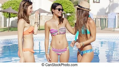Three cute laughing women in bikinis